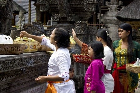 deity: BALI, INDONESIA - JULY 7 2012: Balinese women giving offers to the Deity at Tirta Empul site in Ubud