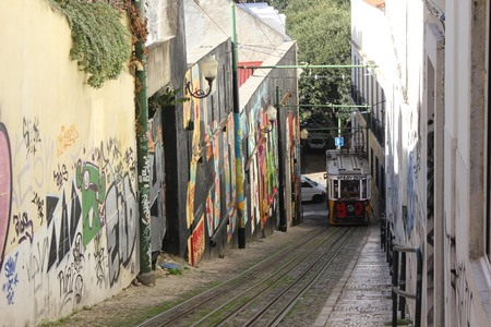 ascensor: LISBON, PORTUGAL - OCTOBER 25 2014: Lisbon Lavra funicolar arriving on the narrow street full of graffiti Editorial
