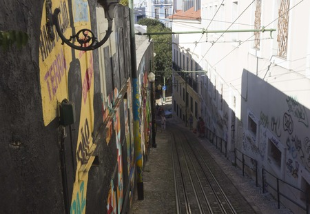 ascensor: The very narrow and slope Lavra Street in Lisbon, Portugal, with graffiti on the wall Editorial
