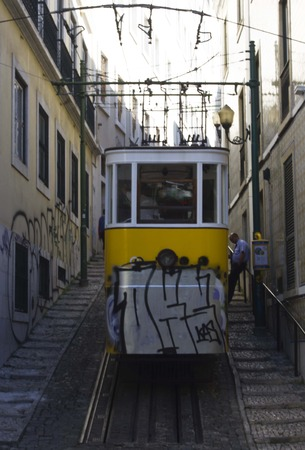 ascensor: LISBON, PORTUGAL - OCTOBER 25 2014: Beginning of the route of Lavra Funicular in Lisbon, all drown with graffiti, with stairs on the side of the narrow street