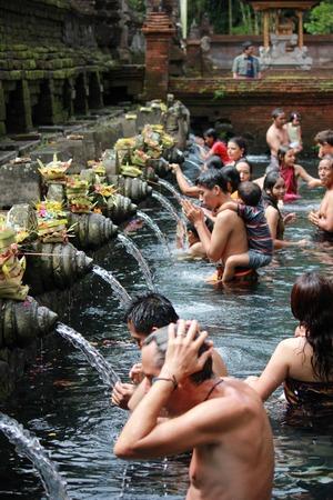 personas banandose: Bali, Indonesia - 7 JULY 2012: La gente se baña en Sagradas Fuentes de Tirta Empul en Bali Editorial