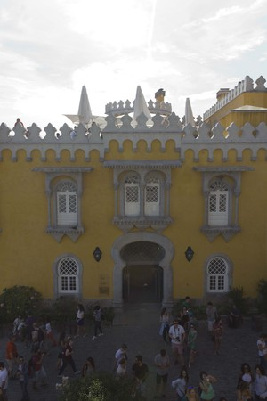 sintra: SINTRA, PORTUGAL - OCTOBER 25 2014: Backlit frontal view of Pena national Palace in Sintra, Portugal, with people on the square Editorial
