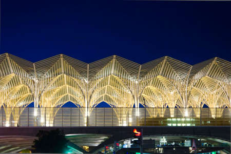 lighted: LISBON, PORTUGAL - OCTOBER 24 2014: Vasco da Gama Shopping Center in Lisbon, view of the external facade lighted with a train passing
