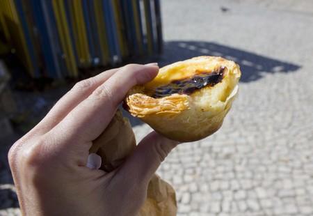nata: Human han hanging a bite Pastel De Nata, Traditional Portuguese sweet, in Sintra, Portugal