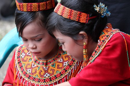 toraja: TANA TORAJA, INDONESIA - JULY 3 2012: Portrait of two young Torajan girls in traditional costume at a funeral ceremony