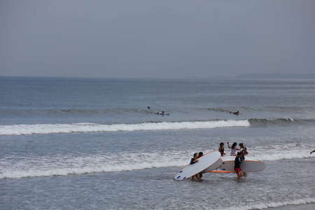 kuta: BALI, INDONESIA - JULY 13 2012: Group of people doing surf on Kuta beach in Indonesia Editorial