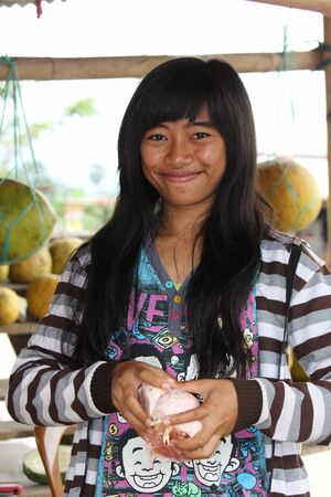 celebes: SULAWESI, INDONESIA - JULY 2 2012: Young Indonesian Fruit seller in the South Sulawesi, cleaning fruit