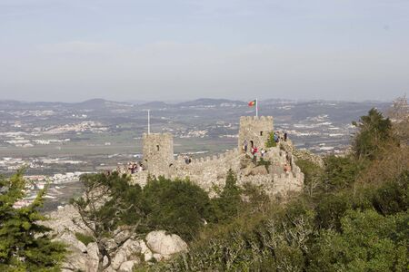 moors: SINTRA, PORTUGAL - OCTOBER 25 2014: Overview of Castle of the Moors and Sintra cityscape and valley from the top of the hill, with people on the Castles tower in the background Editorial