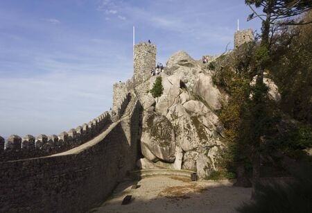 perimeter: SINTRA, PORTUGAL - OCTOBER 25 2014: Beautiful view of Moorish Castle tower and walls perimeter through rocks, with people along the tower Editorial