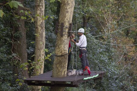 tall tree: SINTRA, PORTUGAL - OCTOBER 25 2014: Man on an elevated platform at work cleaning a tall tree in Castle of the Moors garden