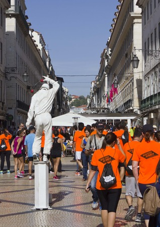 participant: LISBON, PORTUGAL - OCTOBER 26 2014: Participant at Lisbon marathon walking in Rua Augusta after the competition, with a street performer in the middle Editorial