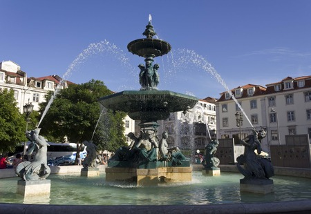 angels fountain: LISBON, PORTUGAL - OCTOBER 23 2014: Monumental fountain in Rossio Square in Lisbon, with few people around and a bus in the background Editorial