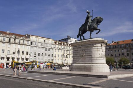 baixa: LISBON, PORTUGAL - OCTOBER 26 2014: Equestrian statue of King John I in the Praca da Figueira, Lisbon, with few people around, and a bird on its head