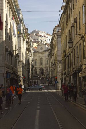 madalena: LISBON, PORTUGAL - OCTOBER 26 2014: Rua conceicao street in Lisbon, with Magdalene church in the background an people walking around Editorial