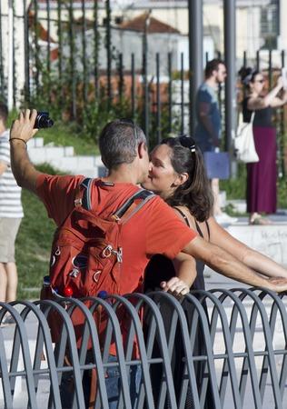 enamorados besandose: LISBOA, Portugal - 23 de octubre 2014: Dos turistas besar mientras que hace una selfie con la c�mara, en Sanata Catarina punto de vista en Lisboa