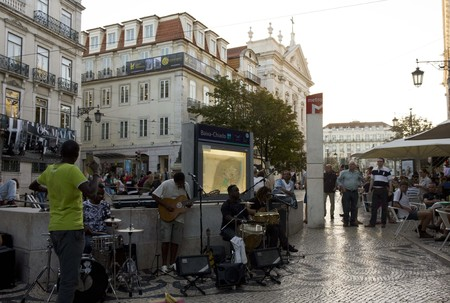 chiado: LISBON, PORTUGAL - OCTOBER 23 2014: Baixa Chiado metro station in Lisbon, with street  performers singing at sunset time with Nossa senhora church in the background