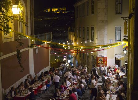 chiado: LISBON, PORTUGAL - OCTOBER 23 2014: People having dinner outdoor in Calcada do Duque in Lisbon, with Sao Jorge Castle in the background