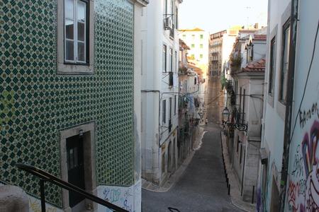 bairro: LISBON, PORTUGAL - OCTOBER 25 2014: Traditional narrow street in Baixa quartier in Lisbon, with green azulejos on the wall