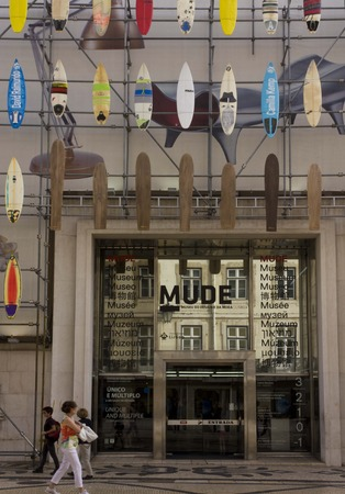 sailboard: LISBON, PORTUGAL - OCTOBER 24 2014: The facade of Muse Museum of Fashion and design in Rua Augusta in Lisbon, with surfboards on the facade and person walking on the street. Editorial