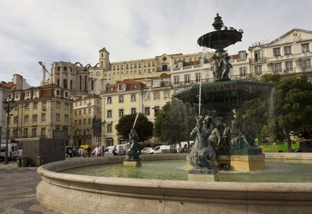 angels fountain: LISBON, PORTUGAL - OCTOBER 24 2014: The monumental fountain in Rossio square in Lisbon, with Carmo Convent in the background Editorial