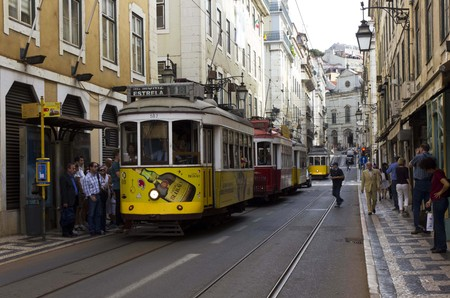 LISBON, PORTUGAL _ OCTOBER 24 2014: Rua Conceicao street in Lisbon with a series of tram and people walking, with Magdalene church in the background
