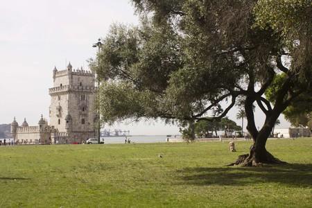 belem: View from the distance of Belem Tower in Lisbon, with trees in the foreground Editorial