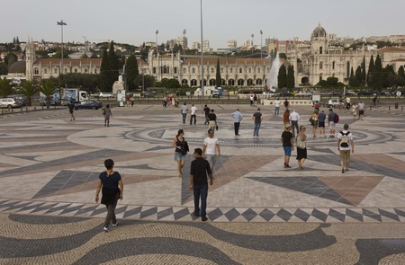 compass rose: LISBON, PORTUGAL - OCTOBER 24 2014: People walking on the floor wind rose of Belem, with Jeronimos Monastery in the background