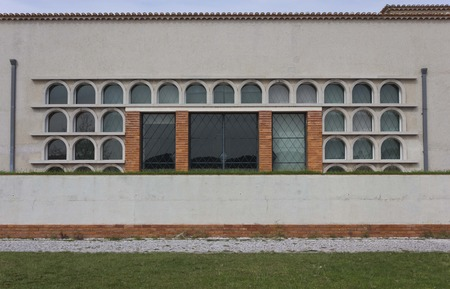particular: LISBON, PORTUGAL - OCTOBER 24 2014: Particular building in Lisbon along Tagus river in Belem, done in bricks, concrete with arched small windows