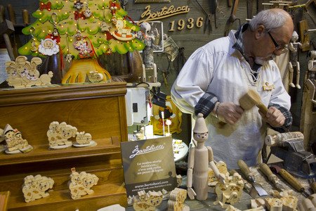 pinocchio: ROME, ITALY - DECEMBER 30 2014: Traditional craftsman carving wood in Pinocchio shape in a shop in Rome