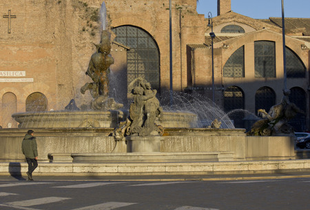 angels fountain: ROME, ITALY - DECEMBER 30 2014: Close up of the fountain in Piazza della Repubblica in Rome, with the Basilica of St. Mary of the Angels behind and a man walking Editorial
