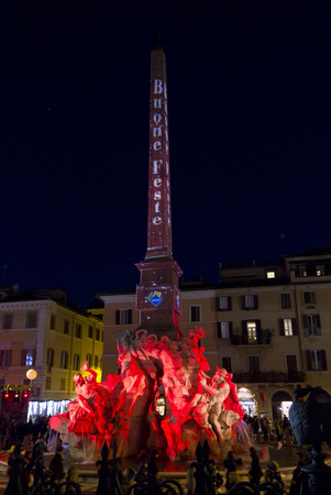lighted: ROME, ITALY - DECEMBER 30 2014: Architectural close up of the Fountain of the four Rivers and obelisk in Rome, lighted by night with the text Happy Holidays in Italian Editorial