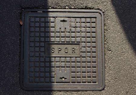 ROMA, ITALIA - 31 DE DICIEMBRE DE 2014: pozo de acceso romano con la abreviatura latina SPQR en la calle de hormigón, la mitad en el sol y la mitad en la sombra