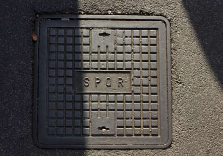 spqr: ROME, ITALY - DECEMBER 31 2014: roman manhole with the latin abbreviation SPQR on the concrete street, half in sun and half in shadow Editorial
