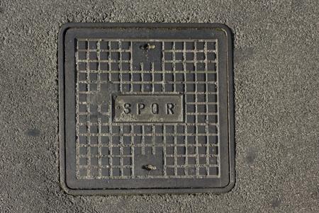 spqr: ROMA, ITALIA - 31 de diciembre 2014: alcantarilla romana con la abreviatura latina SPQR en la calle de concreto