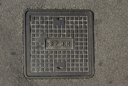 spqr: ROME, ITALY - DECEMBER 31 2014: roman manhole with the latin abbreviation SPQR on the concrete street Editorial