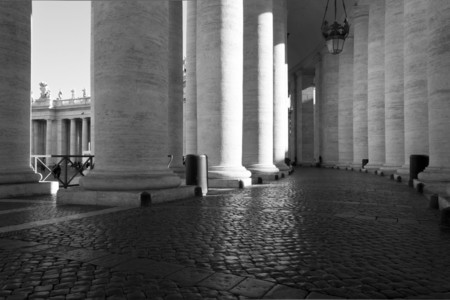 dorian: ROME, ITALY - DECEMBER 31 2014: Architectural close up of the Doric colonnade of Saint Peter Basilica, with its circular shape and cobblestone flooring. Black and white edited Editorial