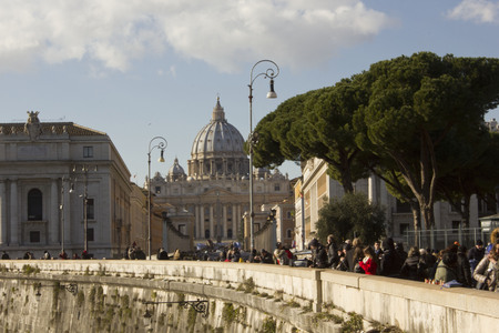 basilica of saint peter: ROME, ITALY - DECEMBER 31 2014: View from the distance of Saint Peter Basilica from Tiber edge, with people on the street.