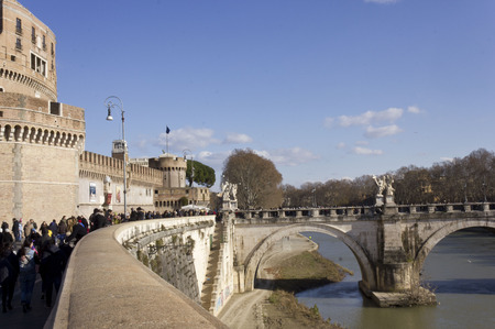 holy angel: ROME, ITALY - DECEMBER 31 2014: People walking on Lungotevere Castello with Castel SantAngelo, its bridge and the Tevere river Editorial