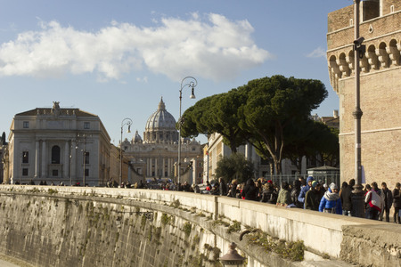 saint peter: ROME, ITALY - DECEMBER 31 2014: View from the distance of Saint Peter Basilica from Tiber edge, with people on the street.