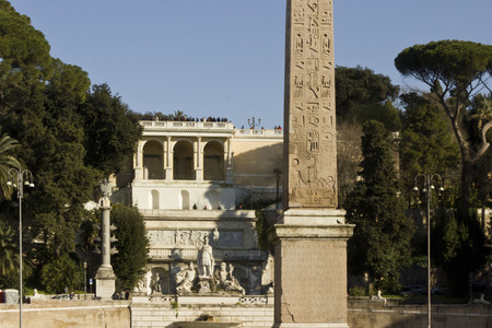 obelisk stone: ROME, ITALY - DECEMBER 31 2014: The Egyptian obelisk of Ramesses II in Piazza del Popolo in Rome, Italy, surrounded by trees, and the Pincian hill in the background