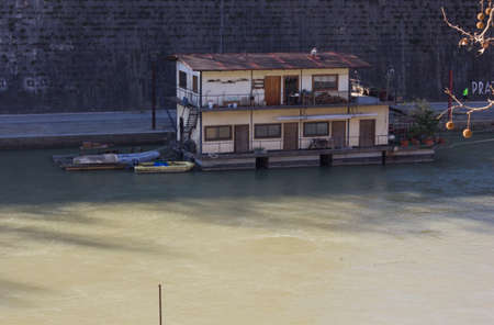 house float on water: ROME, ITALY - DECEMBER 31 2014: Houseboat on Tiber River in Rome, Italy