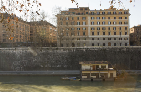 house float on water: ROME, ITALY - DECEMBER 31 2014: Houseboats on Tiber River in Rome, with building in the background, Italy