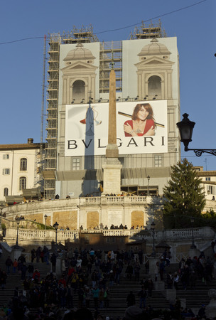 trinita: ROME, ITALY - DECEMBER 31 2014: Day view from of the Spanish steps of Piazza di Spagna with people on it, and the Trinita dei Monti church under renovation works Editorial