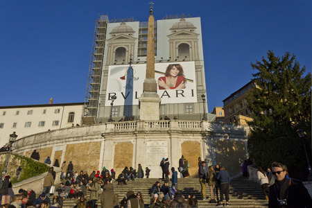 trinita: ROME, ITALY - DECEMBER 31 2014: Day view of the Spanish steps of Piazza di Spagna with people on it, and the Trinita dei Monti church under renovation works