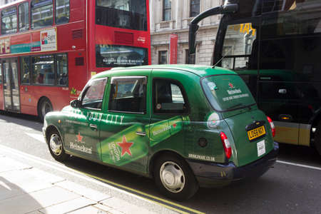 hackney carriage: LONDON, UNITED KINGDOM - SEPTEMBER 11 2015: Heineken Branded taxi cab in the streets of London, United Kingdom