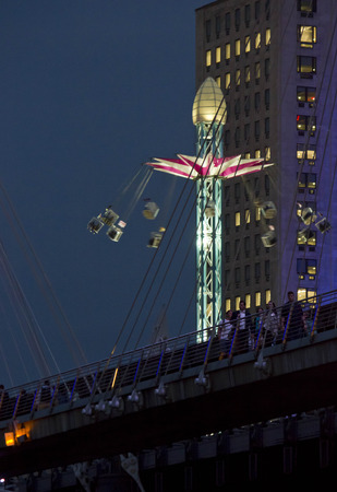 turnabout: LONDON, UNITED KINGDOM - SEPTEMBER 11 2015: Swing Ride Carousel in London at night, behind the bridge