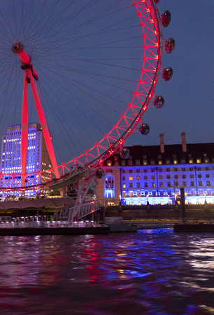 lighted: LONDON, UNITED KINGDOM - SEPTEMBER 11 2015: Night view of the Millenium wheel, lighted in red at twilight