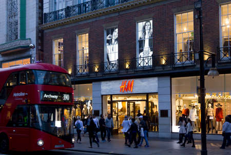 oxford street: LONDON, UNITED KINGDOM - SEPTEMBER 11 2015: H&M shop in Oxford Street in London, with people walking and the traditional red bus