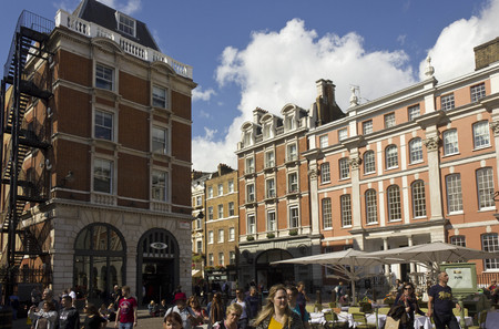 brit: LONDON, UNITED KINGDOM - SEPTEMBER 12 2015: Covent Garden Piazza in London, building around and people