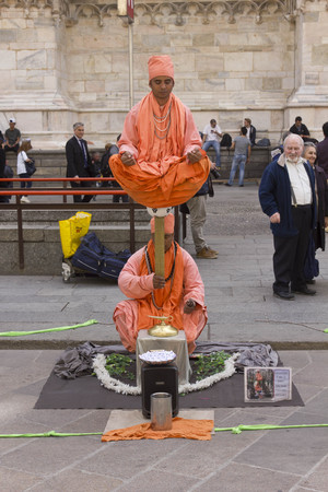 balancing act: MILAN, ITALY - APRIL 14 2015: Unknown street artists in Milan city center, performing a balancing act, and people around